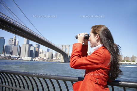 Woman using binoculars near Bridge FYI00900297
