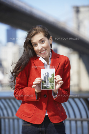 Woman holding Brooklyn Bridge postcard FYI00900303