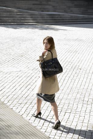 Businesswoman walking across square FYI00900324