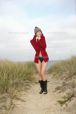 Woman in hat and cardigan on beach FYI00900623