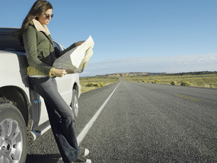 Woman reading road map by car on highway FYI00901011