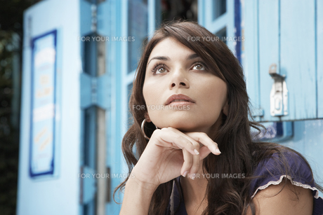 Woman day dreaming with chin on hands FYI00901222