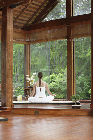 Woman meditating on tatami near windows FYI00901409