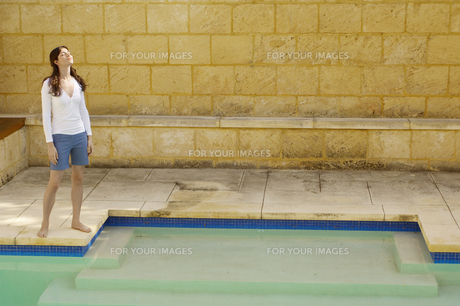 Young woman standing by swimming pool FYI00902405