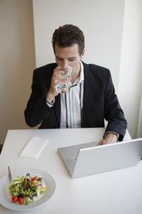 Businessman with laptop eating salad FYI00902711