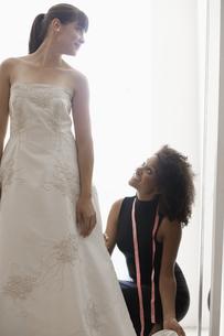 Woman adjusting wedding dress FYI00902979