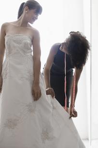 Woman adjusting wedding dress FYI00902993