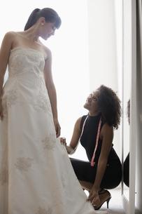 Woman adjusting wedding dress FYI00902999