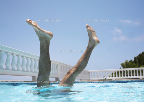Mans legs above water in swimming pool FYI00903525