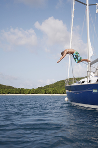 Mid adult man jumping from sailboat FYI00903740
