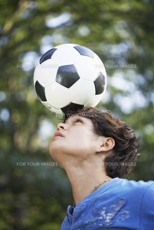 Teenager balancing ball on forehead FYI00903873