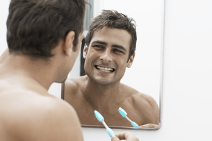 Mid adult man cleaning teeth FYI00903916