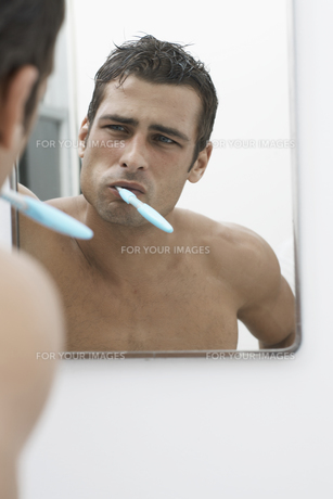 Mid adult man cleaning teeth FYI00903949