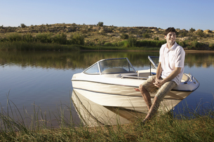 Young man sitting on motorboat FYI00903985
