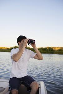 Young man using binoculars at lake FYI00904046