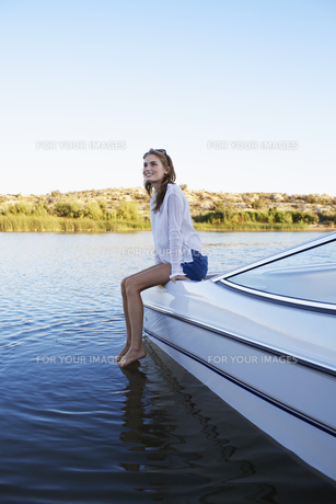Woman sitting at the edge of motorboat FYI00904058