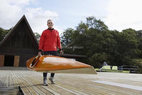 Senior man carrying a kayak FYI00904631