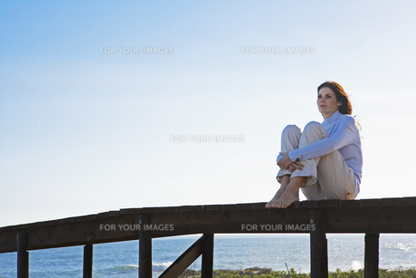 Mid adult woman sitting on jetty FYI00904969