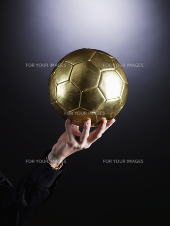 Hand Holding Soccer Ball FYI00906383