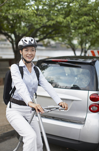 Mid-Adult Woman on Bicycle Beside Smart Car FYI00906846