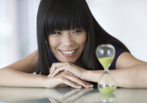 Mid-Adult Woman Looking at Hourglass FYI00906956