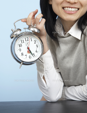 Close-Up of Businesswoman Holding Alarm Clock FYI00907075