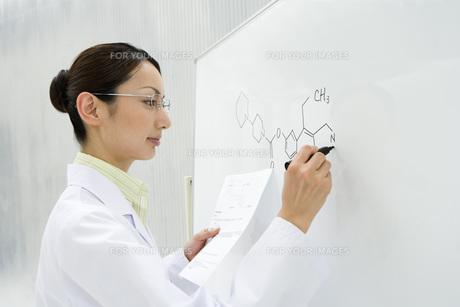 ホワイトボードに書いている女性研究員 FYI00910321