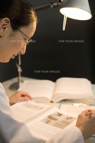 ノートを見る女性研究員 FYI00910364