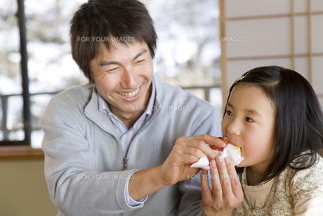 お菓子を食べさせる父親と女の子 FYI00911738