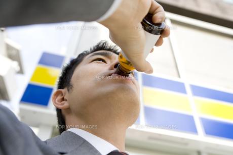 コンビニの前で栄養ドリンクを飲む男性 FYI00912382