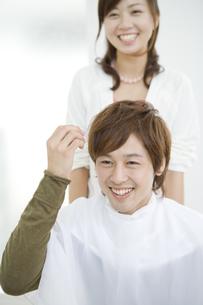ケープをした笑顔の男性と美容師 FYI00913268