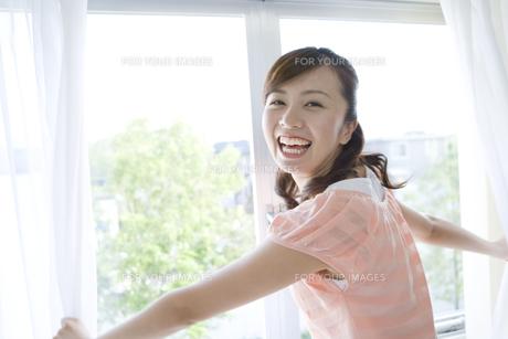 カーテンを開ける笑顔の女性 FYI00913339