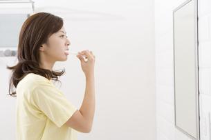 鏡を見て歯磨きをする女性 FYI00913368