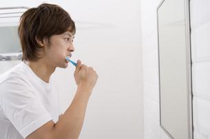 鏡を見て歯磨きをする男性 FYI00913412