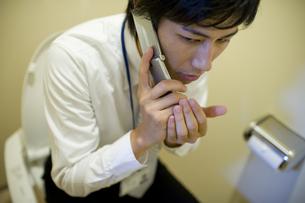 トイレでこっそり電話している男性 FYI00913629
