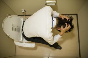 トイレで頭を抱えた男性 FYI00913630