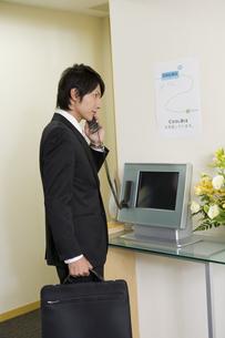 会社の受付で受話器を持った男性 FYI00913635