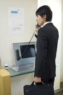 会社の受付で受話器を持った男性 FYI00913637