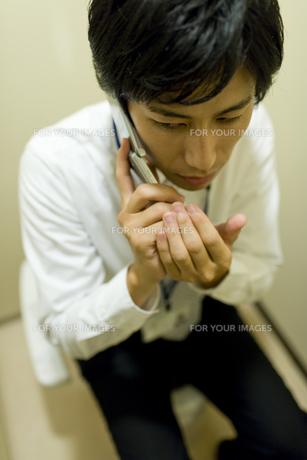 トイレでこっそり電話している男性 FYI00913681