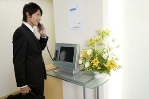 会社の受付で受話器を持った男性 FYI00913718