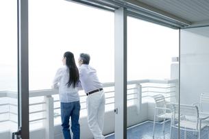 部屋のベランダから外の景色を眺める夫婦 FYI00917783