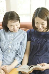 笑顔で本を見るふたりの女性 FYI00918379