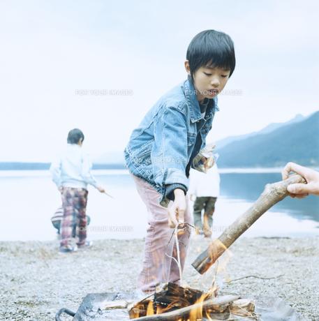 湖畔でおこした焚火のそばで遊ぶ4人の男の子 FYI00920383