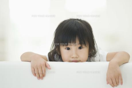 ソファの背もたれから顔を出す女の子 FYI00934586