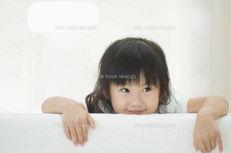 ソファの背もたれから顔を出す女の子 FYI00934593