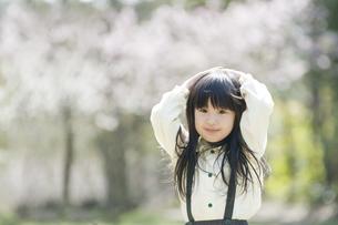 両手を頭に乗せて微笑む女の子 FYI00934727