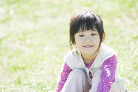 芝生に座って微笑む女の子 FYI00934780