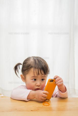 スマートフォンを触る女の子の素材 [FYI00944910]