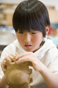 粘土をこねる小学生の男の子の素材 [FYI00945319]