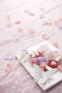 ピンクのレースの上に白いフォトスタンドとマニキュアと花びら FYI00961137